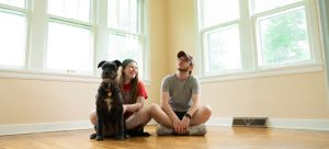 a couple sitting on the floor with their dog in an empty house after checking for moving day mistakes
