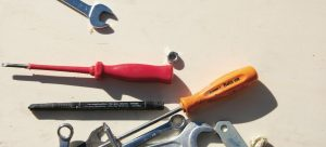 screwdrivers, wrenches and bolts on a white surface
