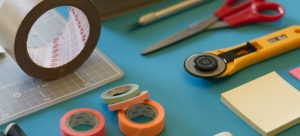 tapes, scalpels and scissors all together on a blue table