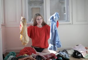 a woman holding two sets of clothes in her hands