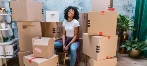 a woman sitting between cardboard boxes after learning which foods should you pack for moving