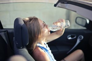 Woman is seating in the car and drinking lot of water from plastic bottle, to avoid dehydration and health hazards when moving during the summer