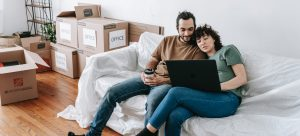 a couple sitting on a couch, doing research on a laptop with boxes behind them