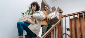 a man and a woman carry moving boxes