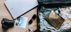 a suitcase with clothes, a wallet and a camera and laptop beside it