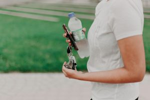 Woman holding a bottle of water to prepare for moving in the heat