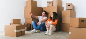 a couple sitting between cardboard boxes