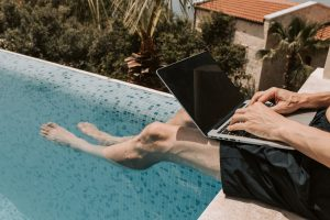 Man sitting next to a swimming pool with a laptop
