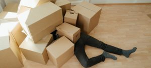 Man lying under the pile of boxes
