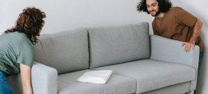 Two people carrying a sofa