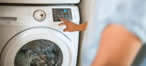 a man turning on the washing machine with clothes inside