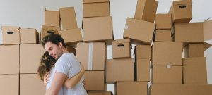 Two people hugging next to a pile of boxes