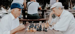 two seniors playing chess in the park