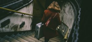 a girl with a suitcase going down the stairs